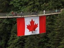 Tourism in Canada: Capilano Suspension Bridge with Canadian Flag. Capilano Suspension Bridge Park with its bridge crossing Capilano River is a popular tourist Royalty Free Stock Photo