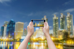 Tourism concept. Hand woman with Smartphone taking a picture of City night at Bangkok, Thailand. Tourism concept Stock Images
