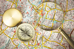 Tourism concept. Magnifying glass with compass on city map Stock Photos