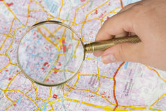 Tourism concept. Womans hand holding magnifying glass above city map Stock Photos