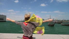 Tourism in Doha city. Tourism in qatar. Blonde caucasian woman with open arms backside at Corniche promenade with Dhow Harbour on background. Lifestyle tourist stock footage
