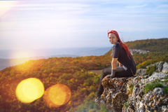 Tourism on top. Beautiful young girl with red hair sitting on the edge of a cliff in the sun Royalty Free Stock Photos