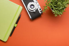 Tourism, travel concept. Office desk table with notepad, camera and supplies. Top view. Copy space for text. Royalty Free Stock Photo