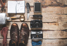 Tourism Travel Equipment With Space. Adventure Discovery Activity Concept. Hiking accessories on wooden background: old hiking leather boots, vintage film camera stock photo