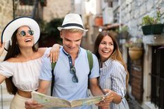 Smiling gorup of friends with map. Tourism, travel, leisure, holidays and friendship concept. Tourism, travel, leisure, holidays and friendship concept - smiling royalty free stock image