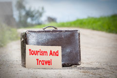 Tourism and Travel. Old traveling suitcase on country road Stock Images