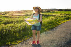 Tourism, travel and summer concept - Happy woman traveler with backpack checks map to find directions. Stock Photography