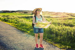 Tourism, travel and summer concept - Happy woman traveler with backpack checks map to find directions. Royalty Free Stock Photos