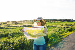 Tourism, travel and summer concept - Happy woman traveler with backpack checks map to find directions. Royalty Free Stock Photography