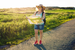 Tourism, travel and summer concept - Happy woman traveler with backpack checks map to find directions. Royalty Free Stock Photo