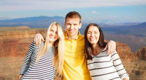 Group of happy friends. Tourism, travel and summer holidays concept - group of happy friends over grand canyon national park background royalty free stock images