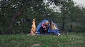 Tourism. Two young people come to the tent near which a fire burns stock video footage