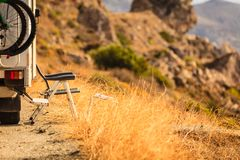 Camper car on nature. Tourism vacation and travel. Camper van with bicyles and camping furnitures on nature in Greece stock image