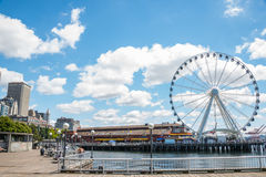 Tourism Waterfront Pier 57 Seattle Washington. SEATTLE, WA - JUNE 24, 2014: Pier 57 with Great Ferris Wheel and Miners Landing, a popular tourist destination on stock image