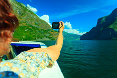 Tourism. Woman with camera on ship, fjord in Norway. Stock Images