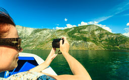 Tourism. Woman with camera on ship, fjord in Norway. Royalty Free Stock Photography