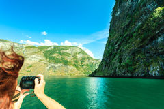 Tourism. Woman with camera on ship, fjord in Norway. Stock Photography