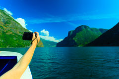 Tourism. Woman with camera on ship, fjord in Norway. Stock Photos