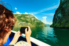 Tourism. Woman with camera on ship, fjord in Norway. Royalty Free Stock Photos