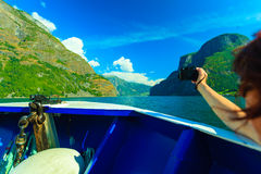 Tourism. Woman with camera on ship, fjord in Norway. Royalty Free Stock Photo