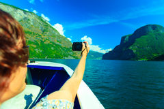 Tourism. Woman with camera on ship, fjord in Norway. Stock Photo