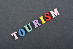 TOURISM word on black board background composed from colorful abc alphabet block wooden letters, copy space for ad text Royalty Free Stock Photo