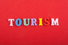 TOURISM word on red background composed from colorful abc alphabet block wooden letters, copy space for ad text Royalty Free Stock Photos