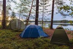 Tourisme campant et tente d'aventures sous le paysage de forêt de vue près de l'eau extérieure en ciel de soirée et de coucher du photographie stock libre de droits