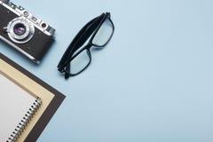 Tourisme, concept de voyage Table de bureau avec le bloc-notes, l'appareil-photo et les approvisionnements Vue supérieure Copiez  Photos libres de droits