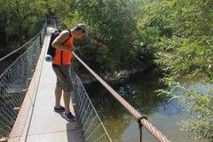 Tourisme d'Eco et concept sain de mode de vie Jeune garçon de randonneur avec le sac à dos Le voyage de voyageur sur le pont susp Photo libre de droits