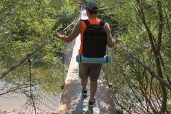 Tourisme d'Eco et concept sain de mode de vie Jeune garçon de randonneur avec le sac à dos Le voyage de voyageur sur le pont susp Images stock