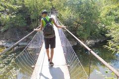 Tourisme d'Eco et concept sain de mode de vie Jeune garçon de randonneur avec le sac à dos Le voyage de voyageur sur le pont susp Images libres de droits