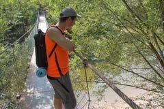 Tourisme d'Eco et concept sain de mode de vie Jeune garçon de randonneur avec le sac à dos Le voyage de voyageur sur le pont susp Photos stock