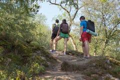 Tourisme d'Eco et concept sain de mode de vie Trois jeunes touristes avec le voyage de sacs à dos Photo stock