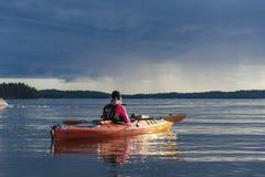 Tourisme de l'archipel kayaking de Stockholm de femme et de rainclouds image stock