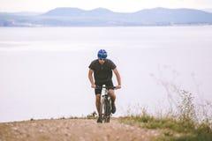Tourisme de thème et recyclage sur faire du vélo de montagne le type monte vers le haut sur une route rocheuse et rocheuse dans l images stock