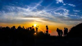 Tourisms en haut de lever de soleil de attente de montagne Photographie stock libre de droits