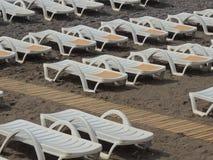 Tourismusstrandsandfreizeit-Sonnenbetten niemand Lizenzfreies Stockfoto