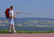Tourist. Standing tourist with backpack and trekking sticks over unfocused background Stock Photos