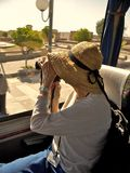 Tourist. Woman tourist on bus in Morocco taking photographs out window royalty free stock image