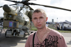 The tourist. Poses on the military helicopter background Stock Image