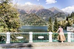 A tourist admires the beauty of lake Ritsa. Royalty Free Stock Photography
