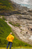 Tourist admiring Boyabreen Glacier in Norway Stock Photo