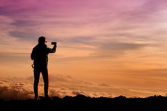 Tourist admiring breathtaking sunset views from the Mauna Kea, a dormant volcano on the island of Hawaii Stock Photos