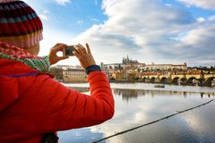 Tourist photographing Prague with Charles Bridge and Hradcany. Tourist admiring fall cityscape of Prague city with Charles Bridge across Vltava and the Hradcany stock images