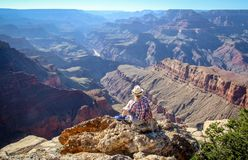 Tourist admiring multicoloured rocks with dozens of layers in Grand Canyon. Magnificent landscape of multicoloured rocks in Grand Canyon, Arizona during Royalty Free Stock Image