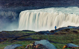 Tourist admiring view of falling water of the most powerful wate. Rfall in Europe - Dettifoss. Jokulsargljufur National Park, Iceland. White nights view Stock Images