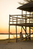 Tourist on African Safari. A young female tourist sits under a thatched roof hut and takes photos of sunset while on safari in the Makgadikgadi Pans, Botswana Stock Photo