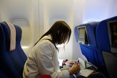 Tourist in an airplane. A woman filling up an arrival document in an airplane Royalty Free Stock Images