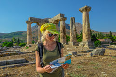 Tourist in Ancient Corinth. Greece tourist woman reads travel guide outdoors. Happy female holding informative guide at Doric Temple of Apollo in Ancient Corinth Royalty Free Stock Photos